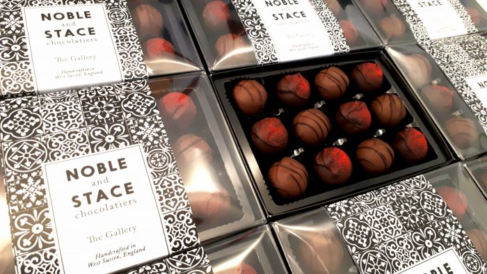 Lots of The Gallery boxes - one open, chocolate truffles with piped decoration, some rose coloured