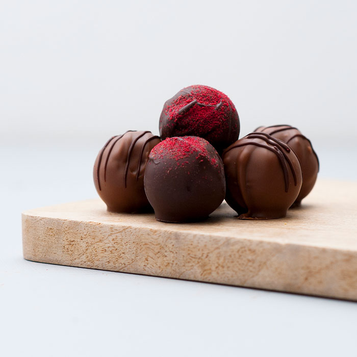A pile of loose milk and dark chocolate truffles decorated with piped chocolate or dusted with red