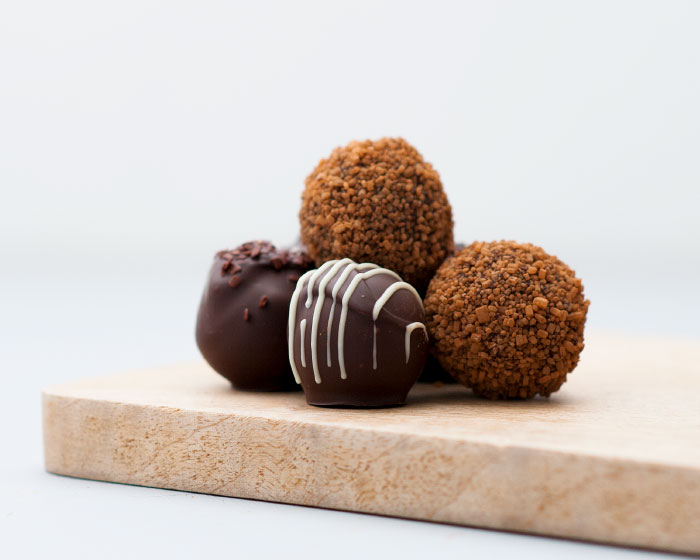 A pile of loose chocolate truffles - decorated with piped and sprinkles of chocolate sitting on a wooden board