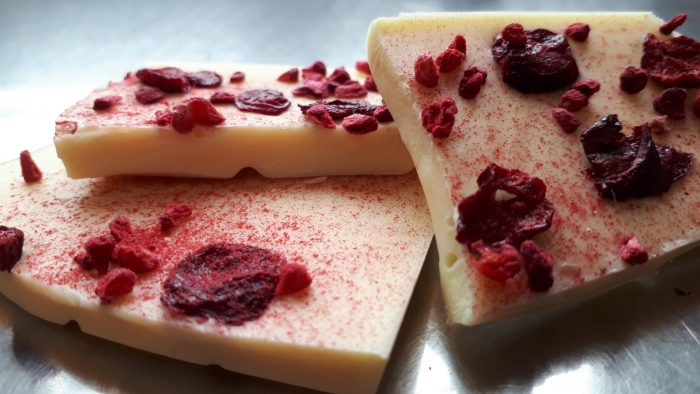 Close up of broken up pieces of white chocolate tablette covered with freeze dried berries