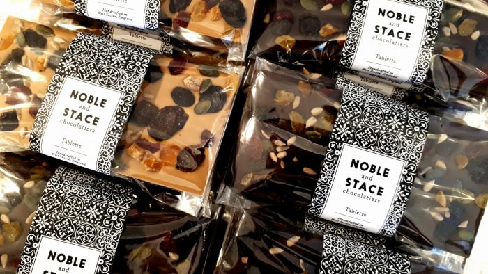Close up of 6 chocolate tablettes covered with fruits and seeds