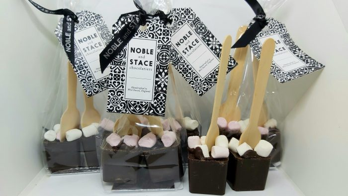 4 clear bags tied with ribbon and Noble and Stace tags, 2 spoons per bag. 2 unpackaged wooden spoons with chocolate cubes and mini marshmallows