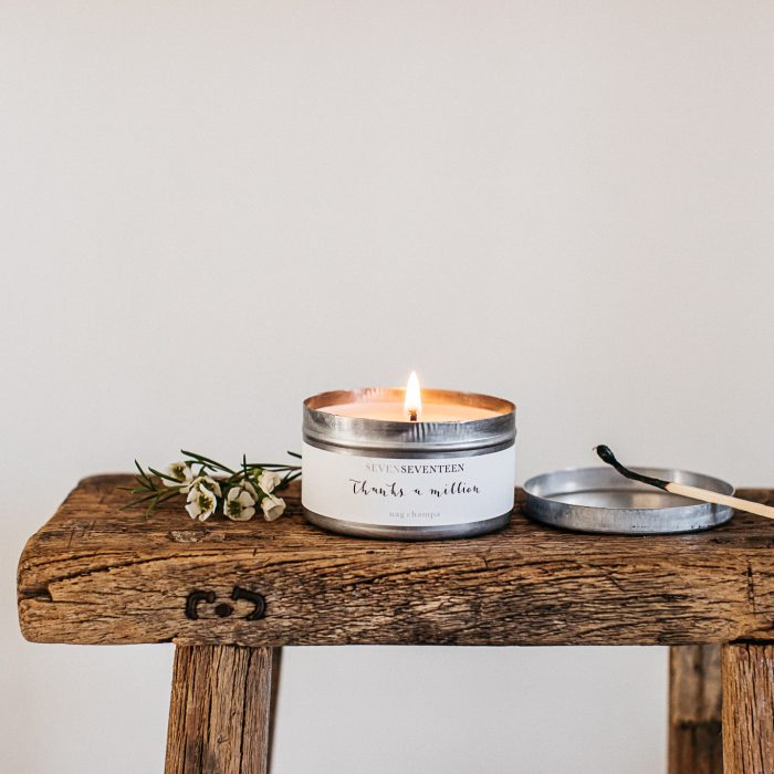 Candle in metal tin with lid on wooden table, white label saying SevenSeventeen Thanks a Million nag champa